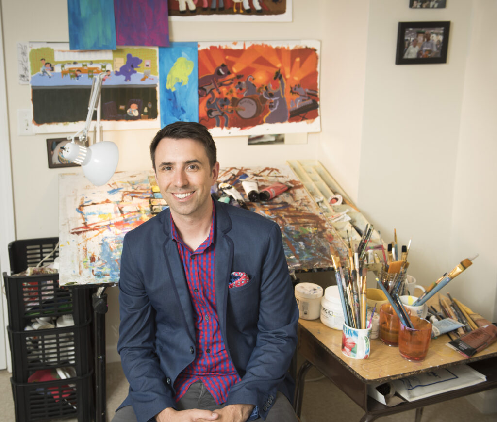 Author Illustrator Jarrett Krosoczka sits in front of his work table covered in paintings. Mugs full of paintbrushes sit next to him and his illustrations are hung on the wall behind him.